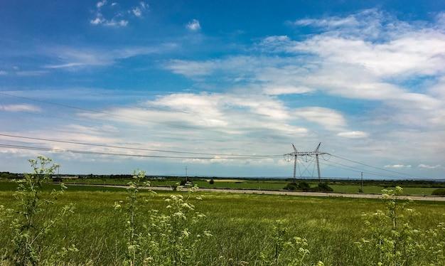 Foto incrível de um belo prado no fundo de uma torre de transmissão