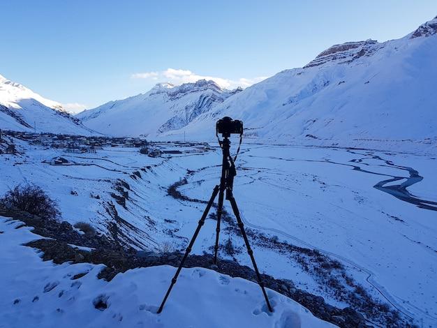 Foto incrível de uma cordilheira coberta de neve no primeiro plano de um suporte para câmera