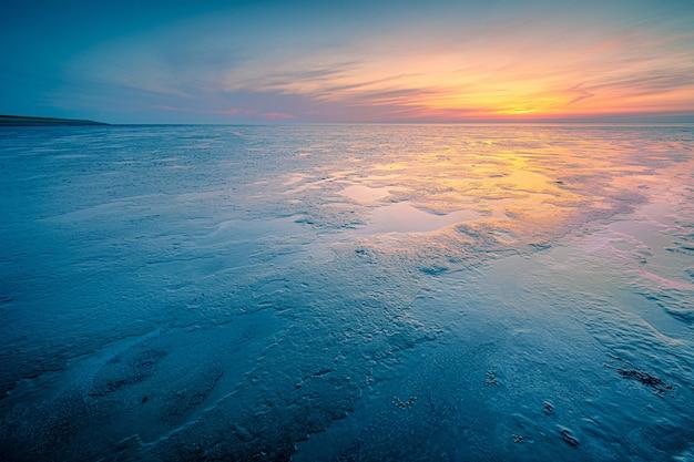 Foto incrível de uma paisagem marinha durante um clima frio no pôr do sol