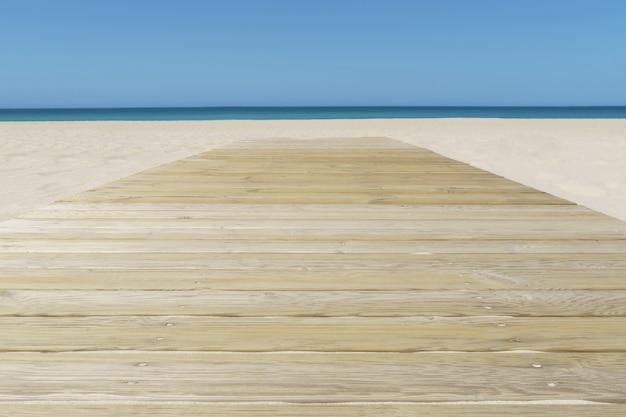 Foto incrível de uma praia de areia com um píer de madeira