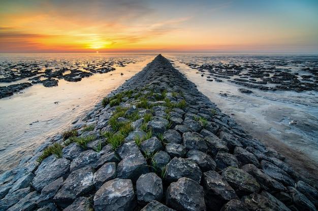Foto incrível de uma praia rochosa à distância do pôr do sol