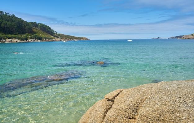 Foto incrível de uma praia rochosa sob o sol