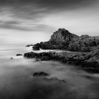 Foto incrível em tons de cinza de uma praia rochosa em guernsey, perto de fort houmet