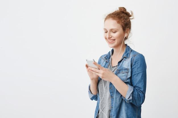 Foto interior da adolescente ruiva linda com cabelo penteado no coque, sorrindo amplamente enquanto envia mensagens de texto ou navega na rede social via smartphone