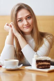Foto interior da atraente mulher loira sardenta passa o dia de folga na cafeteria, bebe café e come bolo saboroso
