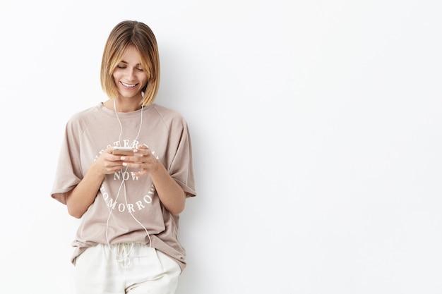Foto interior da bela jovem instrutora de esportes do sexo feminino, relaxando após um treinamento intenso, sorrindo agradavelmente enquanto envia mensagens com o namorado, ouvindo suas faixas favoritas usando wi-fi gratuito