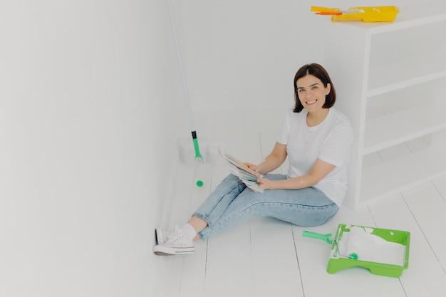 Foto interior da dona de casa morena satisfeita senta-se no chão