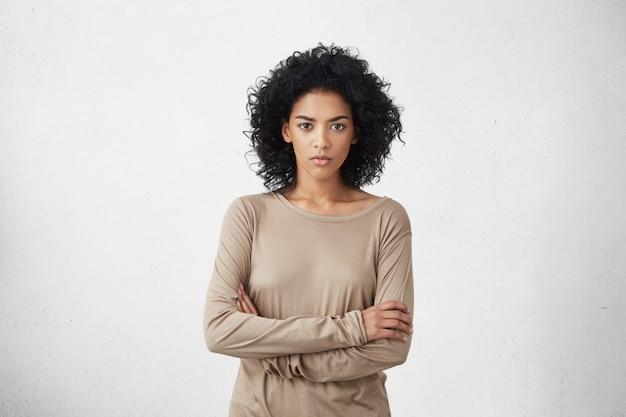 Foto interior da fêmea irritada jovem de raça mista irritada vestida casualmente, mantendo os braços cruzados, olhando com expressão estrita e cética