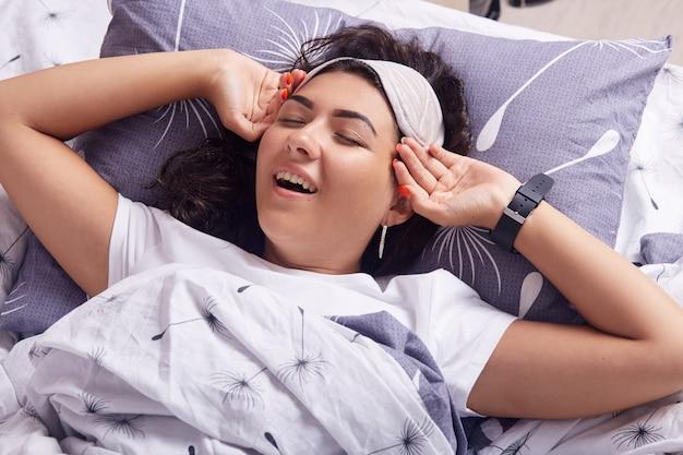 Foto interior da linda garota bocejando na cama depois de dormir, bocejando, adorável mulher mantém os olhos fechados, mantém a mão perto de templos, deitado sob o cobertor, relaxando na manhã, atraente senhora acordando.