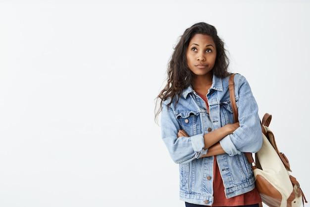 Foto interior da linda garota de pele escura, olhando para longe, tendo expressão no rosto duvidosa e indecisa, perseguindo os lábios como se ela não estivesse satisfeita. fêmea jovem confusa na jaqueta jeans com mochila