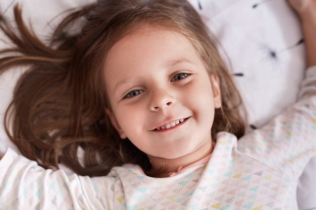 Foto interior da menina deitada na cama no quarto aconchegante, espalhando as mãos, coloca em linho branco com dente de leão, bonita criança do sexo feminino com sorriso encantador
