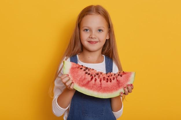 Foto interior da menina encantadora com uma porção de melancia nas mãos dela