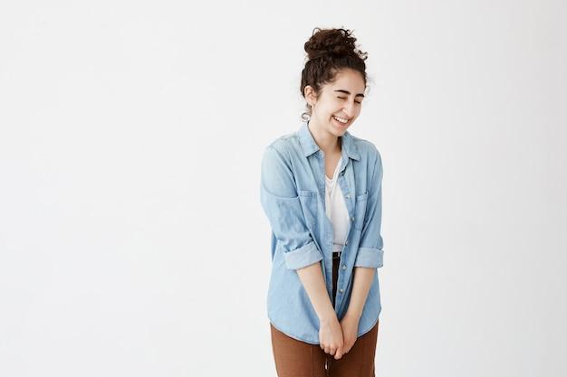 Foto interior da menina tímida estudante bonito com bolo de cabelo sorrindo alegremente, em camisa jeans e calça marrom, satisfeito com o presente. emoções positivas, sentimentos e expressões faciais
