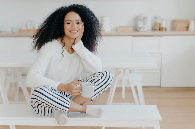 Foto interior da mulher afro-americana bonita usa jumper branco, calça listrada, meias, posa no banco com uma xícara de chá