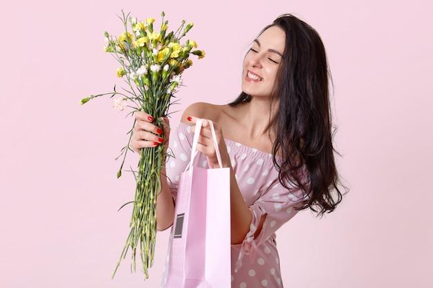 Foto interior de agradável aparência jovem sorri suavemente, vestido elegante vestido, mantém o saco de presente e flores, coloca em rosa claro, estar encantada. conceito de dia das mulheres