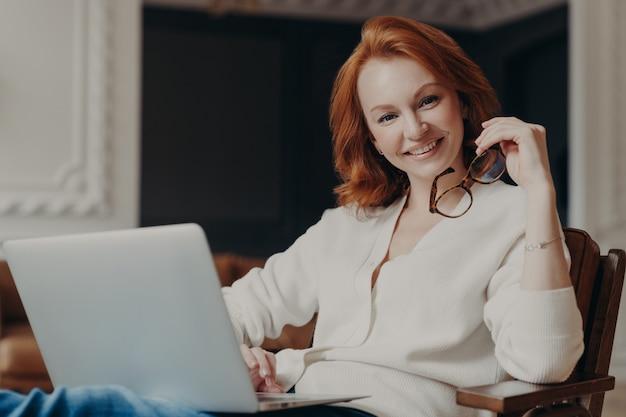 Foto interior de alegre mulher satisfeita trabalha remotamente, ocupado com o trabalho à distância