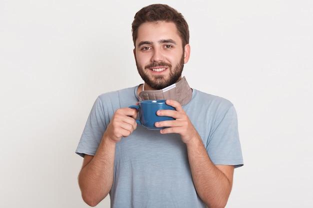 Foto interior de alegre sincero jovem homem com barba, olhando diretamente segurando a xícara com café, tendo um sorriso agradável