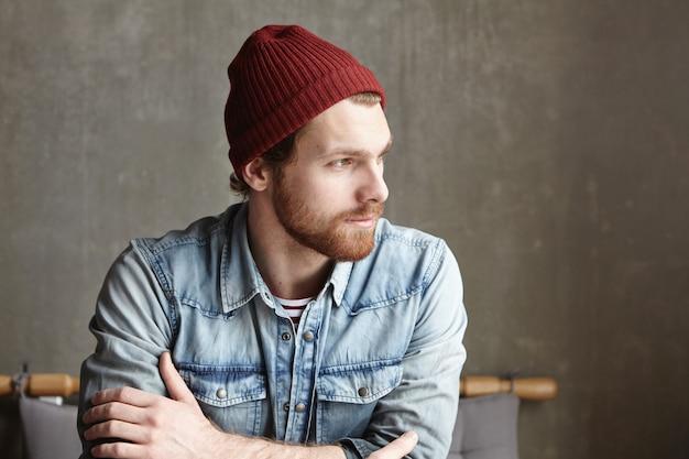 Foto interior de bonito hipster caucasiano barbudo, vestindo chapéu marrom e camisa jeans, sentada no café, olhando para longe com expressão pensativa no rosto, imaginando o que o futuro lhe reserva.