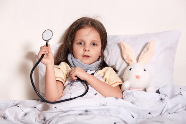 Foto interior de criança do sexo feminino aguarda médico pediatra para examinar as meninas