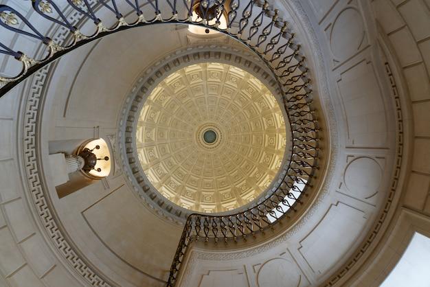 Foto interior de escadas em espiral com um teto esculpido