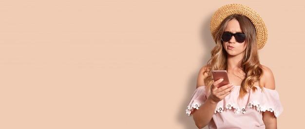 Foto interior de hesitante mulher europeia com expressão sem noção, usa tons da moda e chapéu de verão, mantém o telefone móvel, isolado no bege com espaço de cópia para o seu anúncio