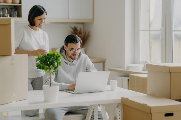 Foto interior de homem e mulher feliz passam a manhã em sua nova cozinha