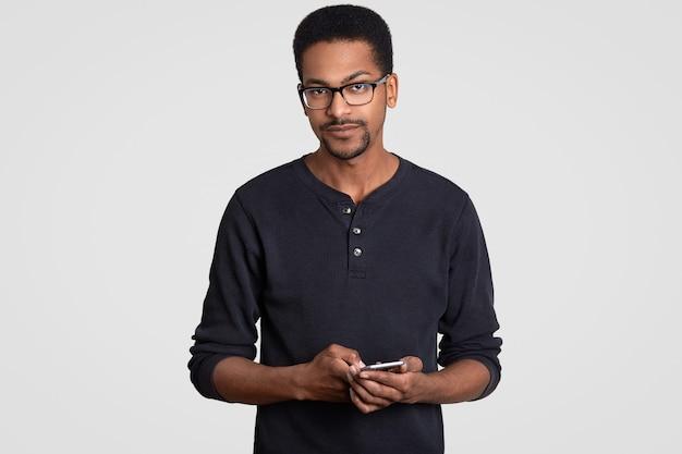 Foto interior de homem sério com pele escura, tem expressão facial confiante, detém celular moderno, textos sms, lê feedback, usa óculos