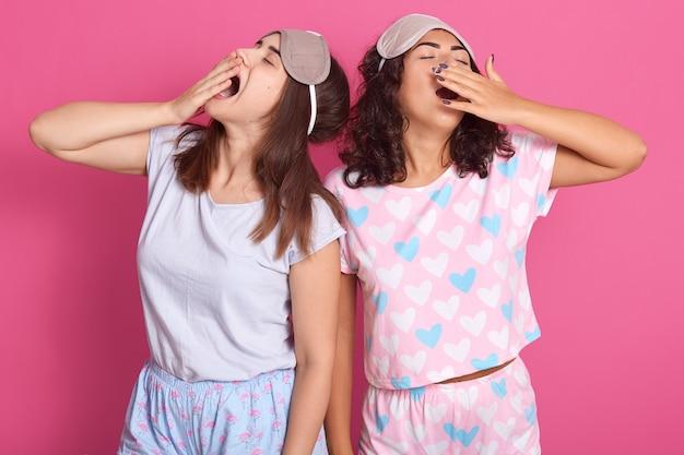 Foto interior de jovens mulheres atraentes de pé contra a parede rosa studio