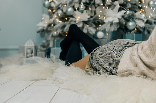 Foto interior de moda de linda mulher linda com cabelos loiros no vestido luxuoso, posando no quarto com árvore de natal e decorações