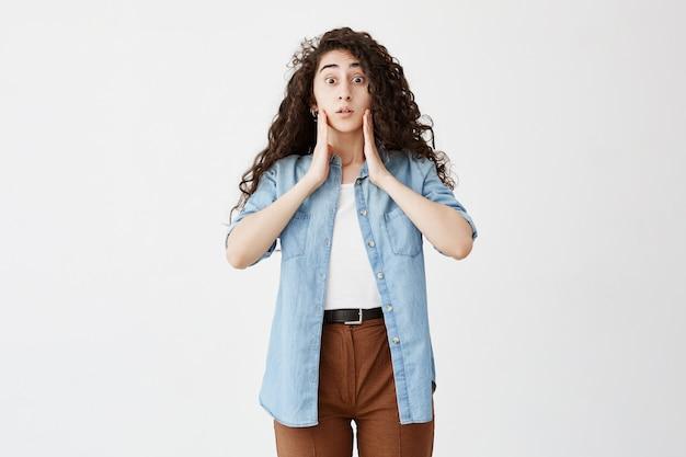 Foto interior de mulher aterrorizada, usando cabelos longos e ondulados, solta, vestida com camisa jeans e calça marrom, mantém as mãos nas bochechas, esquece de fazer a atribuição. menina chocada com olhos estalados