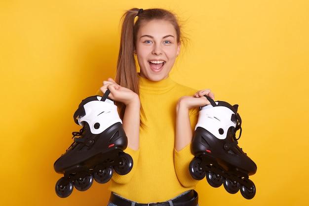 Foto interior de mulher excitada com rabo de cavalo, segurando patins nas mãos