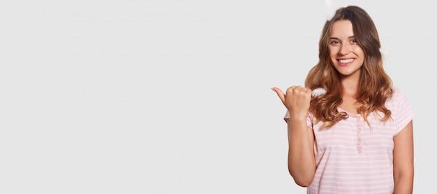 Foto interior de mulher relaxada de aparência agradável anuncia algo, aponta com o polegar para o espaço em branco da cópia, mostra espaço livre para o seu conteúdo promocional, tem um sorriso atraente no rosto
