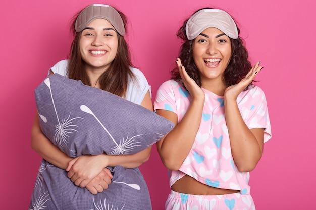 Foto interior de mulheres sorridentes com máscaras para dormir na cabeça, vestindo pijama em pé isolado sobre o estúdio rosa