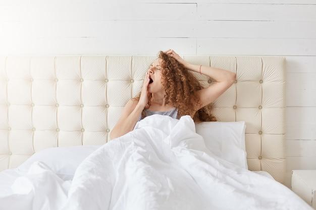Foto interior de pacífica jovem atraente relaxante na cama na manhã
