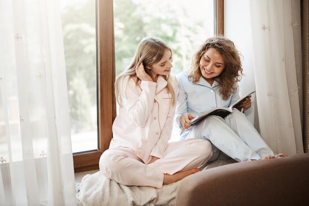 Foto interior de relaxadas felizes caucasianas irmãs sentadas em casa no peitoril da janela em pijamas bonitos, lendo artigos na revista, discutindo as últimas tendências na indústria da moda ou escolhendo roupas novas