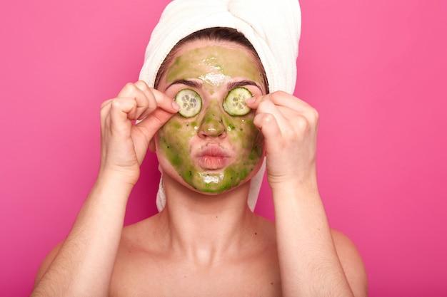 Foto interior de uma jovem mulher atraente com uma máscara verde no rosto, colocando partes de pepino nos olhos, saliente os lábios, tendo o corpo nu, usa uma toalha branca no cabelo, relaxando o tempo de spa.