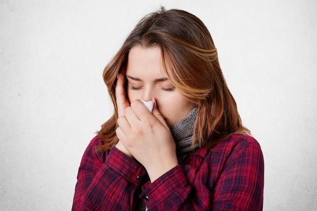 Foto interior de uma mulher com febre e dor de cabeça, usa tecido e espirra o tempo todo, tem coriza e enxaqueca, pegou vírus sazonal