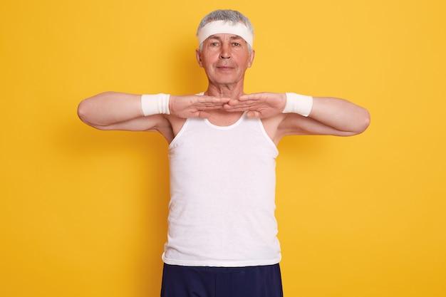 Foto interior do homem desportivo sênior, vestindo camiseta sem mangas e bandana, mantendo as mãos na frente do peito, fazendo exercícios físicos