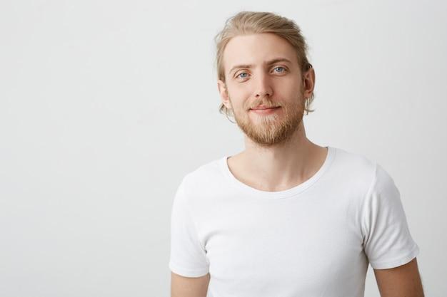 Foto interior do homem loiro caucasiano bonito positivo com barba e bigode sorrindo