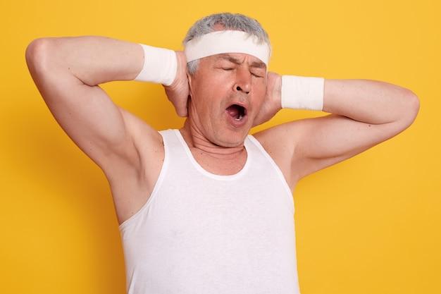 Foto interior do homem sênior bocejando, mantendo as mãos para cima, mantém a boca aberta e os olhos fechados, parece sonolenta depois de praticar esportes