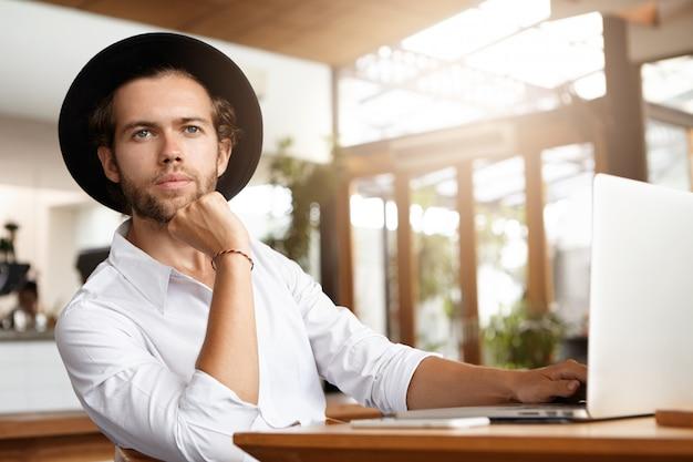 Foto interior do jovem e bonito blogueiro em chapelaria trabalhando em um novo post para seu blog usando wi-fi no pc laptop genérico, segurando a mão no queixo e olhando para a frente com expressão pensativa