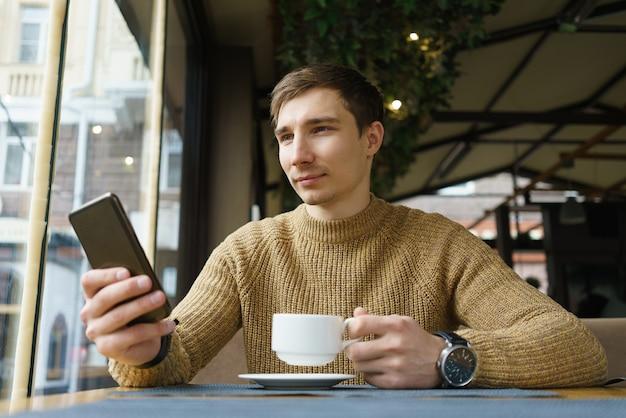 Foto interior do jovem sentado na cafeteria, lendo a mensagem de texto no celular.
