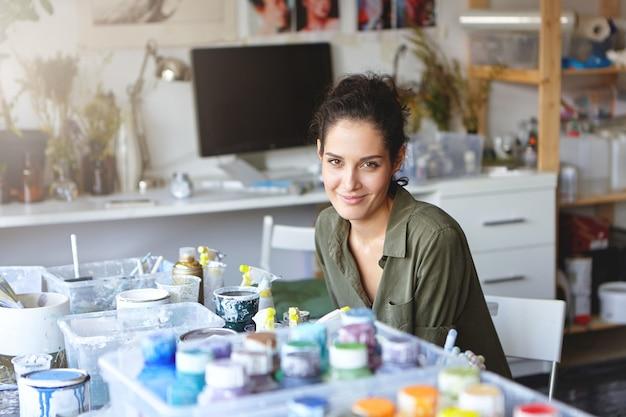 Foto interior do pintor feminino criativo com aparência bonita, sentado à mesa, rodeada de óleos coloridos, olhando com expressão de alegria