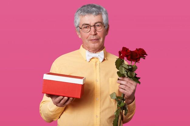 Foto interior do senhor idoso com expressão facial séria detém caixa de presente e rosas vermelhas