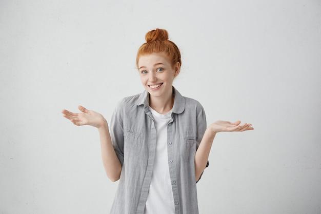 Foto interna da bela ruiva caucasiana de 20 anos com um nó no cabelo, encolhendo os ombros e sorrindo amplamente, sentindo-se confusa ao se recusar a sair com um cara que ela não gosta