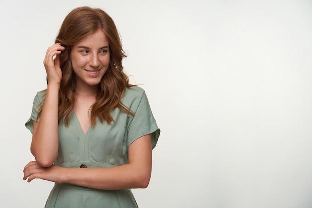 Foto interna da bela ruiva com um sorriso tímido, olhando para o lado e tocando seu cabelo, posando em um vestido vintage