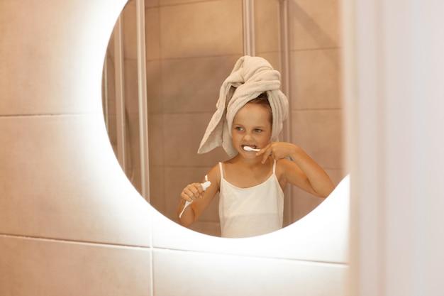 Foto interna da encantadora garotinha escovando os dentes no banheiro em frente ao espelho, espremendo a pasta de dente de um tubo, sorrindo alegremente.