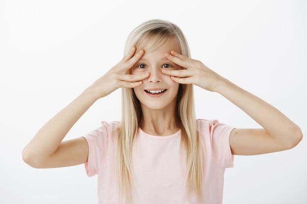 Foto interna da filha fofa espantada e surpresa com um largo sorriso feliz, segurando os dedos perto dos olhos e sorrindo de cena positiva, sendo alegre, participando de uma grande festa em sua homenagem sobre a parede cinza