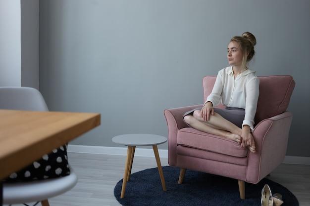 Foto interna da linda jovem empresária europeia cansada com penteado bagunçado, sentada descalça em uma poltrona confortável, vestindo roupas formais de escritório, relaxando depois do trabalho, massageando os pés