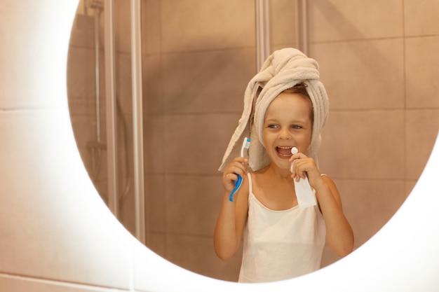 Foto interna da menina escovando os dentes no banheiro, olhando seu reflexo no espelho com uma expressão facial animada, vestindo camiseta branca e enrolou o cabelo na toalha.